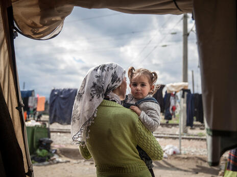 A mother holds her toddler daughter and looks out from their tent on a cloudy day in a refugee camp in Idomeni, Greece.