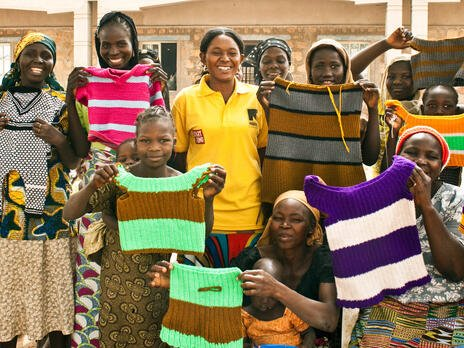 A group of women who are part of an IRC livelihoods program in Nigeria stand outside, lifting hand-knitted tops to show them off.