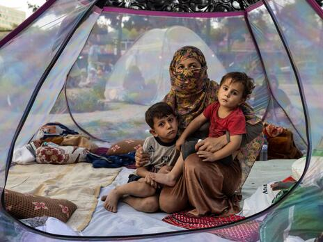 A recently widowed Afghan woman, 28, sits on the floor of a net tent holding holding her two children in a makeshift camp for displaced families in Afghanistan.