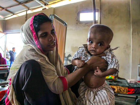 A Rohingya refugee woman holds her malnourished baby in an IRC-supported health center in Bangladesh.