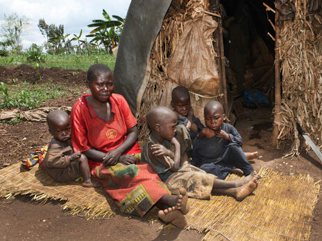 A Burundian woman and four children sit on the ground outside of their hut.