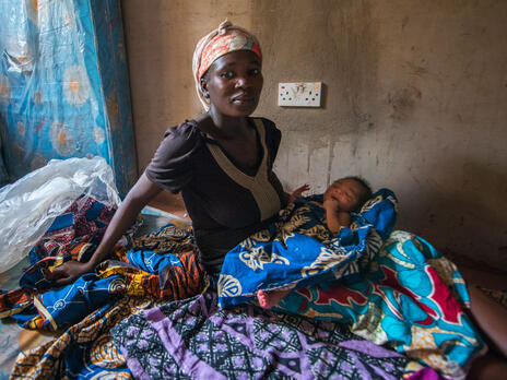 A Nigerian woman sits on a mattress with her infant child.