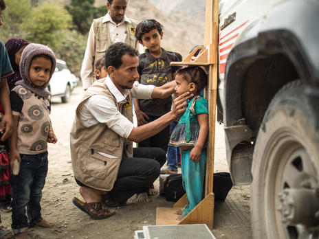 An IRC health worker measures a child in a remote Yemen village for signs of malnutrition.