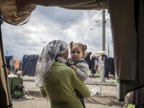 Mother and child stand inside a tent in a refugee center in Greece