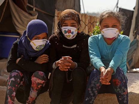 Three refugee children sit on the ground next to one another. They are all wearing masks and looking directly at the camera.