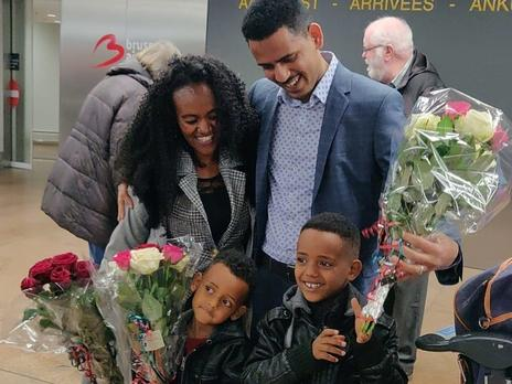 In an airport, a mother and father stand next to each other with their two young boys in front of them. The boys are holding flowers. The parents are looking down at the boys and smiling.