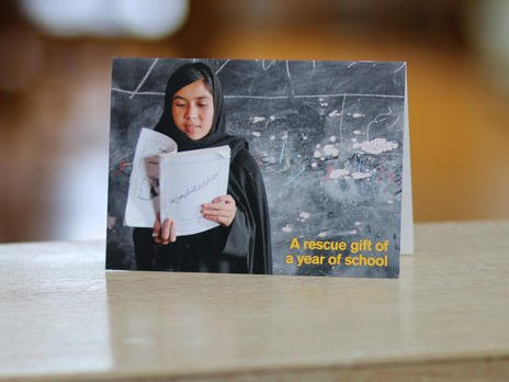 "Card for ""A Year of School"" Rescue Gift, showing a girl in Afghanistan reading at a blackboard"