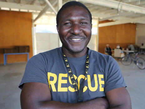 An IRC volunteer wearing a shirt that says RESCUE and an IRC lanyard.