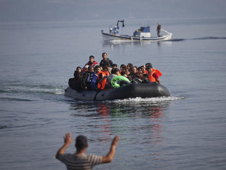 Refugees and migrantsapproach the coast of the Greek island of Lesbos in a crowded rubber raft