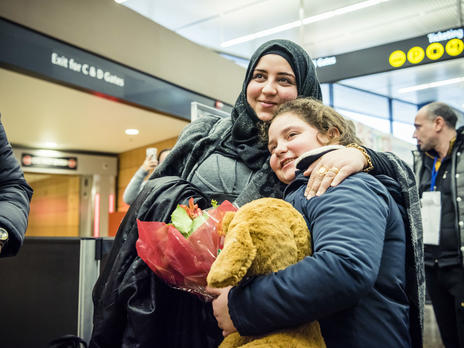 Syrian sisters hug after being reunited at the airport in Seattle