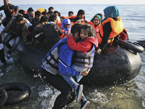 A man carries a child to shore after a raft overflowing with refugees reaches Greece