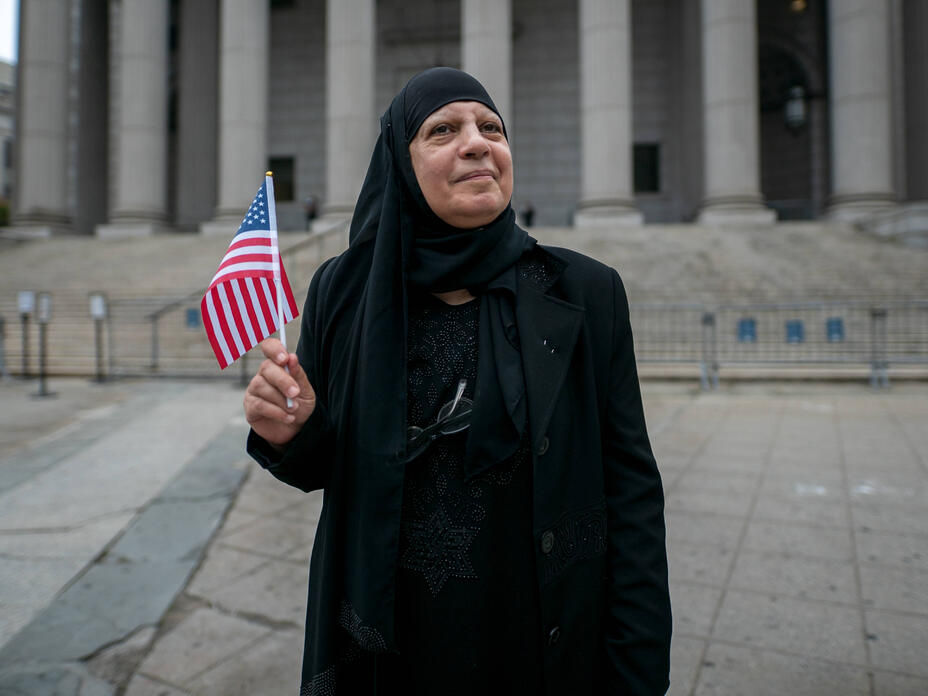 Maha al-Obaidi holds an American flag while standing in front of the courthose where she got her citizenship.