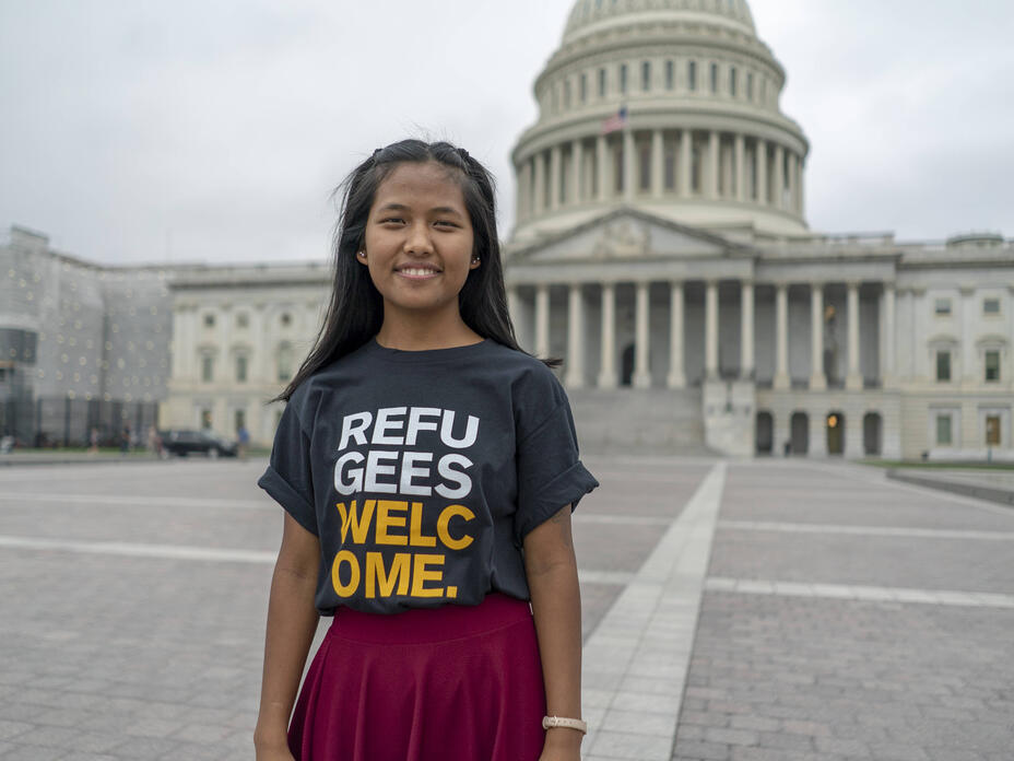 Nuam San, wearing a shirt that says Refugees Welcome, stands in front of the U.S. Capitol building.