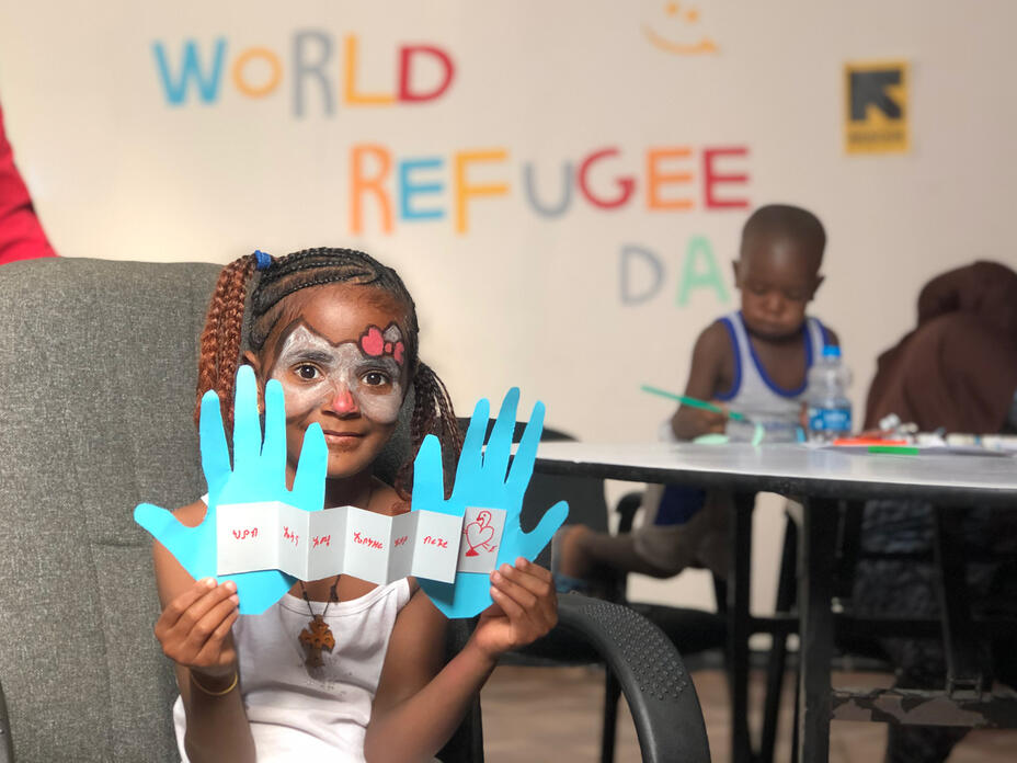 A young girl holds up a piece of artwork. The words World Refugee Day are on the wall behind her and other children work on their artwork at a table.