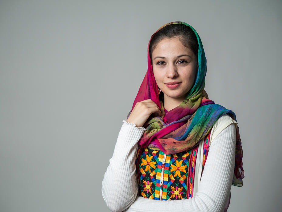 Wearing a brightly colored scarf and other clothes, Muska poses in front of a grey background.