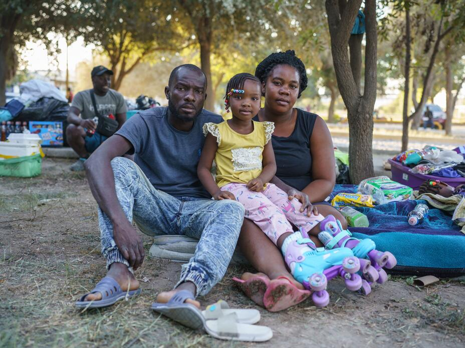 In a makeshift encampment in Mexico, a Haitian family--a mom, dad and young daughter--look straight at the camera while sitting on the ground next to their suitcases and blankets.