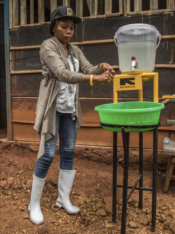 Dr. Sylvie Musema Ngimba washes her hands with chlorine and water