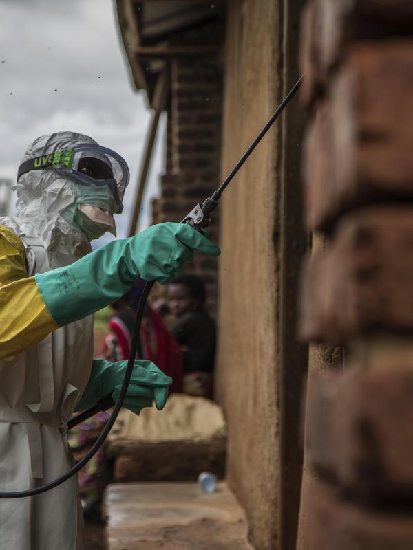 A health worker sprays disinfectant on Case Du Salut health facility