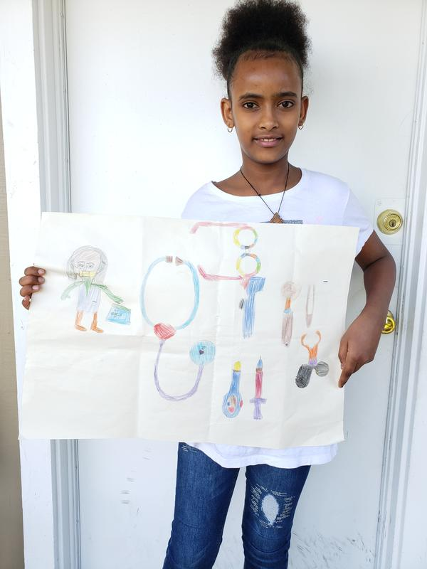 Delina, an 8-year-old girl from Eritrea, stands outside her new home in Seattle holding her drawing of a doctor with her medical implements.