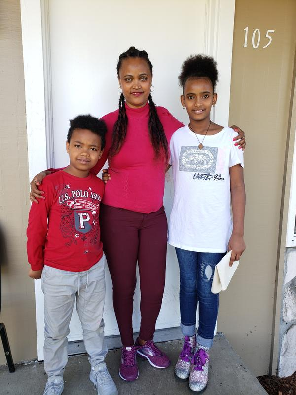 Eritrean mother Abrehet stands with her arms around the shoulders of her 5-year-old son Kudus and daughter Delina, 8.