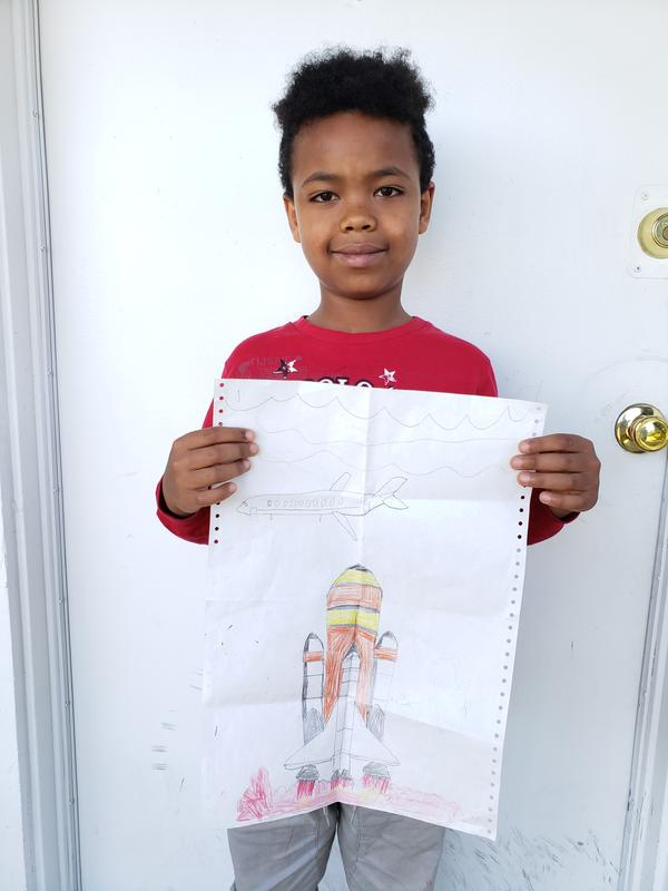 Kudus, a 5-year-old boy from Eritrea, stands outside his new home in Seattle holding his picture of a space shuttle rocket launch.