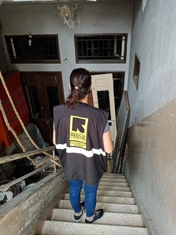 An IRC staff member on the stairway of Assad's building with its blasted-out windows and doors