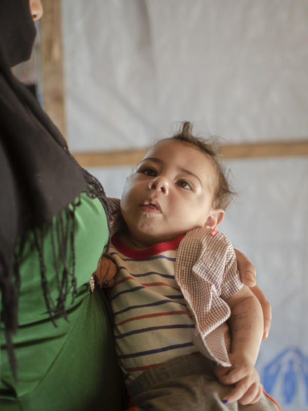 Syrian mother and refugee, Khitam, holds her baby son Brahim