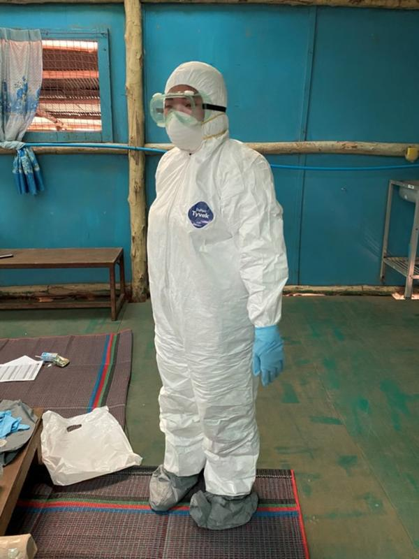 A refugee medic stands inside in a room. They are wearing full personal protective equipment, or PPE, including a white suit, blue gloves, and goggles.