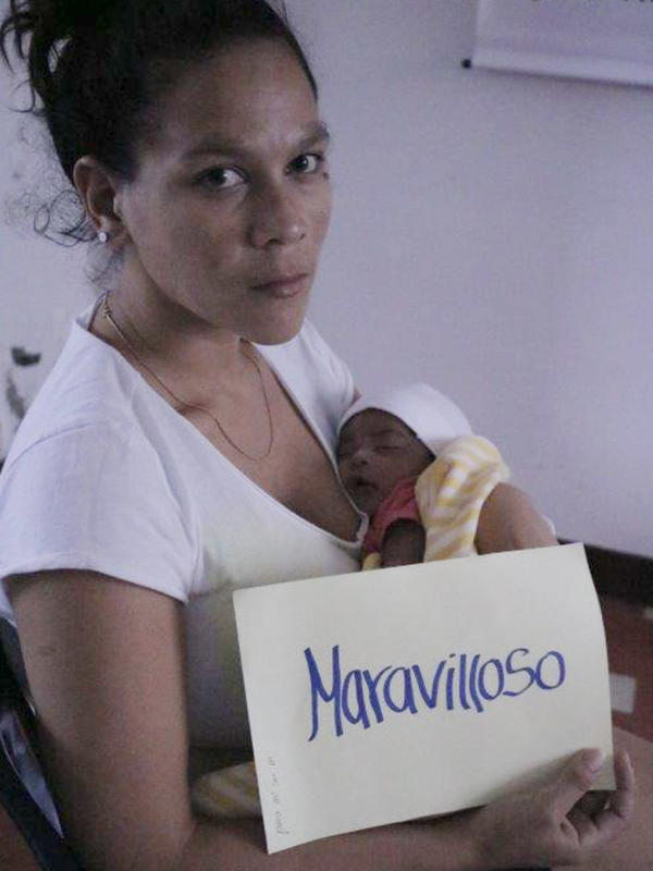 "Verónica Andrade, a Venezuelan migrant in Colombia and a new mother, holds a sign saying ""Maravilloso"" (or ""Wonderful"") along with her new baby while looking at the camera."