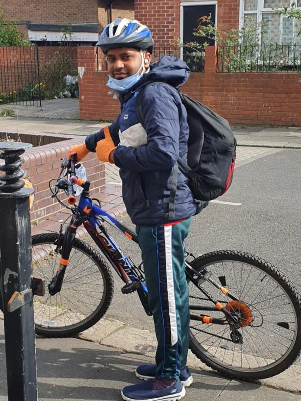 Md Mominul Hamid stands next to his bike and gives a thumbs up. He is wearing a blue helmet and orange gloves and a black backpack.