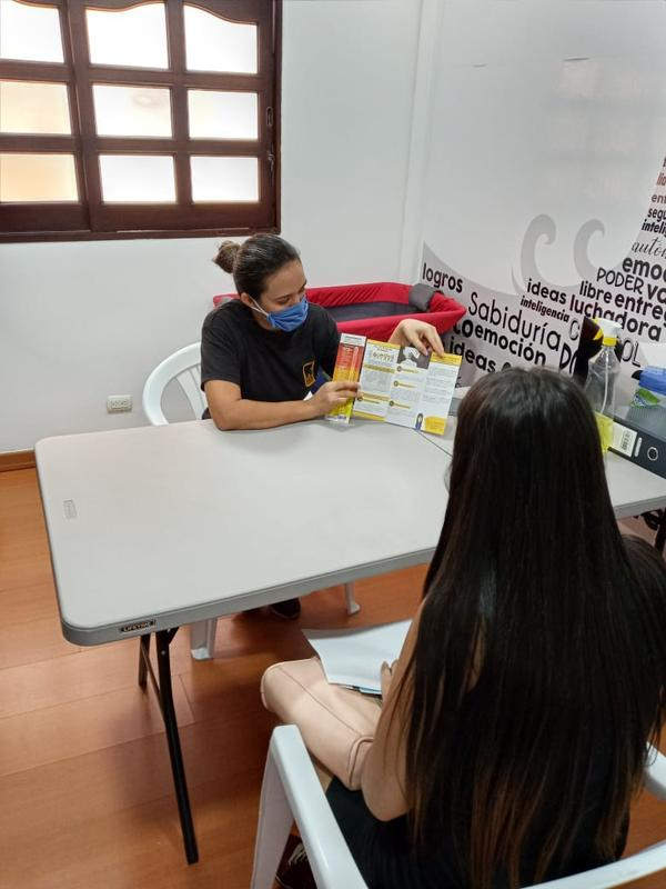 IRC staff in Medellín provide gender-based violence services to women. An IRC staff member sits at a white table holding open literature and explaining IRC's gender-based violence services to a woman.