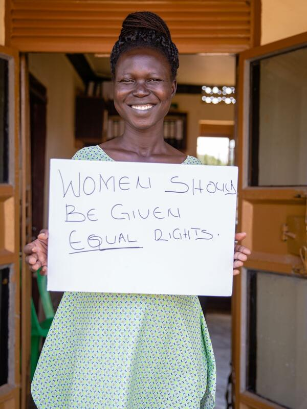 "Grace Muuduru, smiling and looking at the camera, holds a sign that says ""Women should be given equal rights"""