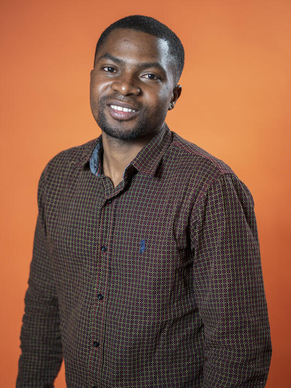Robert Sebatware poses in front of an orange background