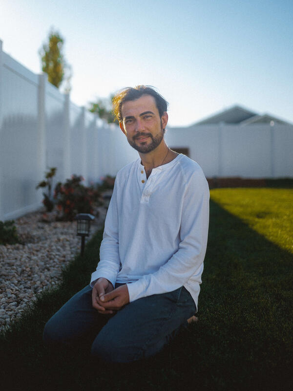 Shadi, wearing a white botton-down shirt, sits in his backyard in front of his white fence near his garden.