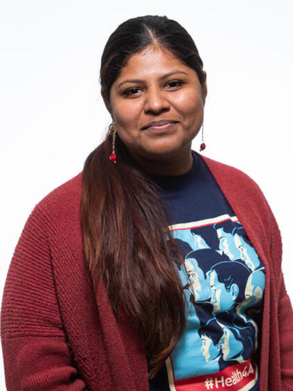 Lupe, a DACA recipient is wearing a red sweater with her hair in a ponytail. She is looking at the camera and standing in front of a white background.