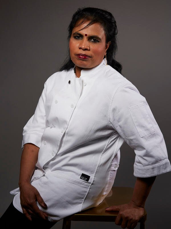 Chef Shanthini, wearing her chefs coat, sits on a stool and looks at the camera.