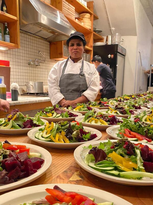Wearing an apron, Chef Shanthini stands behind a table in a kitchen with many plates of a salad.