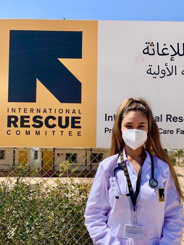Wearing a mask, Dr. Rose Al-Nsour stands outside in front of an IRC logo.