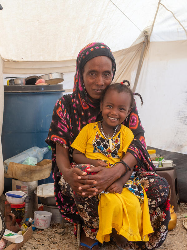 Mulu crouches on the floor of a tent, holding her daughter, after fleeing the Tigeay crisis,