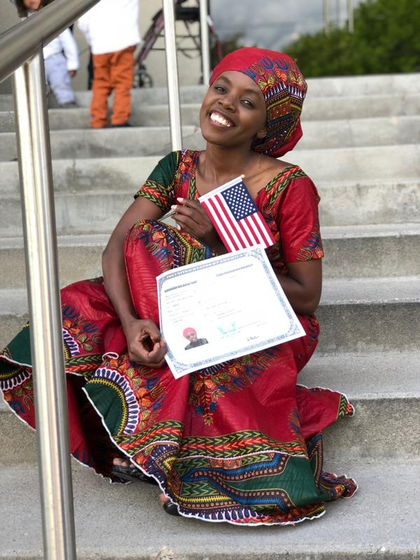Noella sits to celebrate her accomplishment of becoming a U.S. Citizen