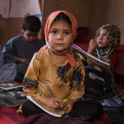 Five children sit on the ground in a school with books and school supplies surrounding them. One girl sits in the foreground on the photo and looks at the camera while holding a notebook.