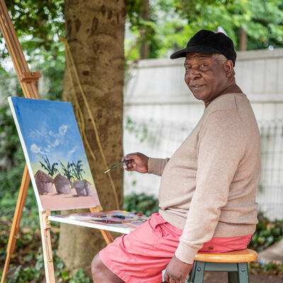 Chishimba sits on a stool in front a painting on an easel outside.