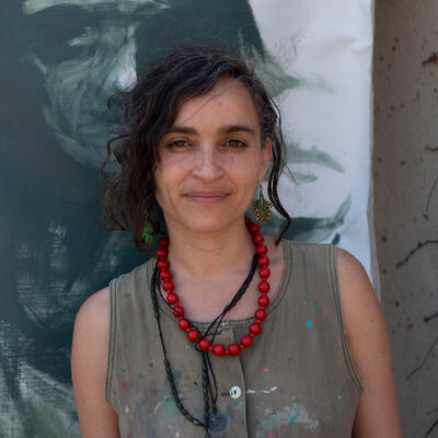 Wearing a red necklace, Diala Brisly poses in front of a painting outside for a World Refugee Day 2021 photo shoot..