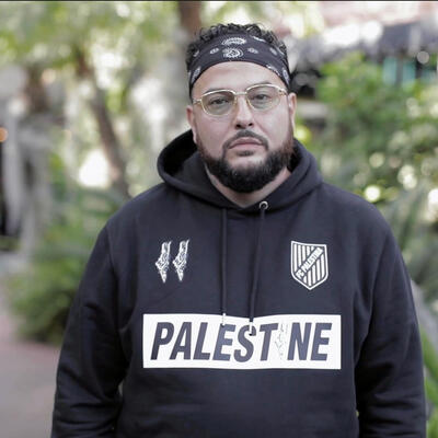 """Wearing a shirt that says """"Palestine,"""" Belly poses outside for a World Refugee Day 2021 photo shoot.."""