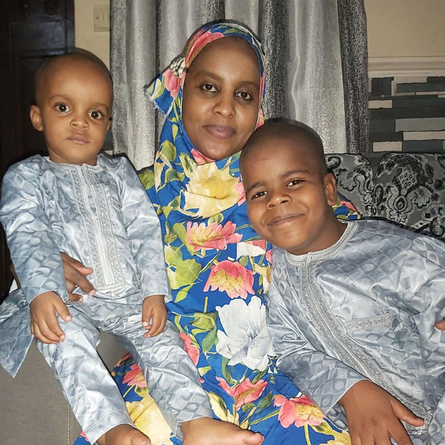 Dr Fatima Ibrahim Lawan poses with her children on either side of her as she sits on a couch.