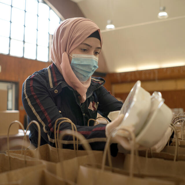 Rania Abou, wearing a mask, stands behind a table filled with paper bags and adds pre-packaged meals to them.
