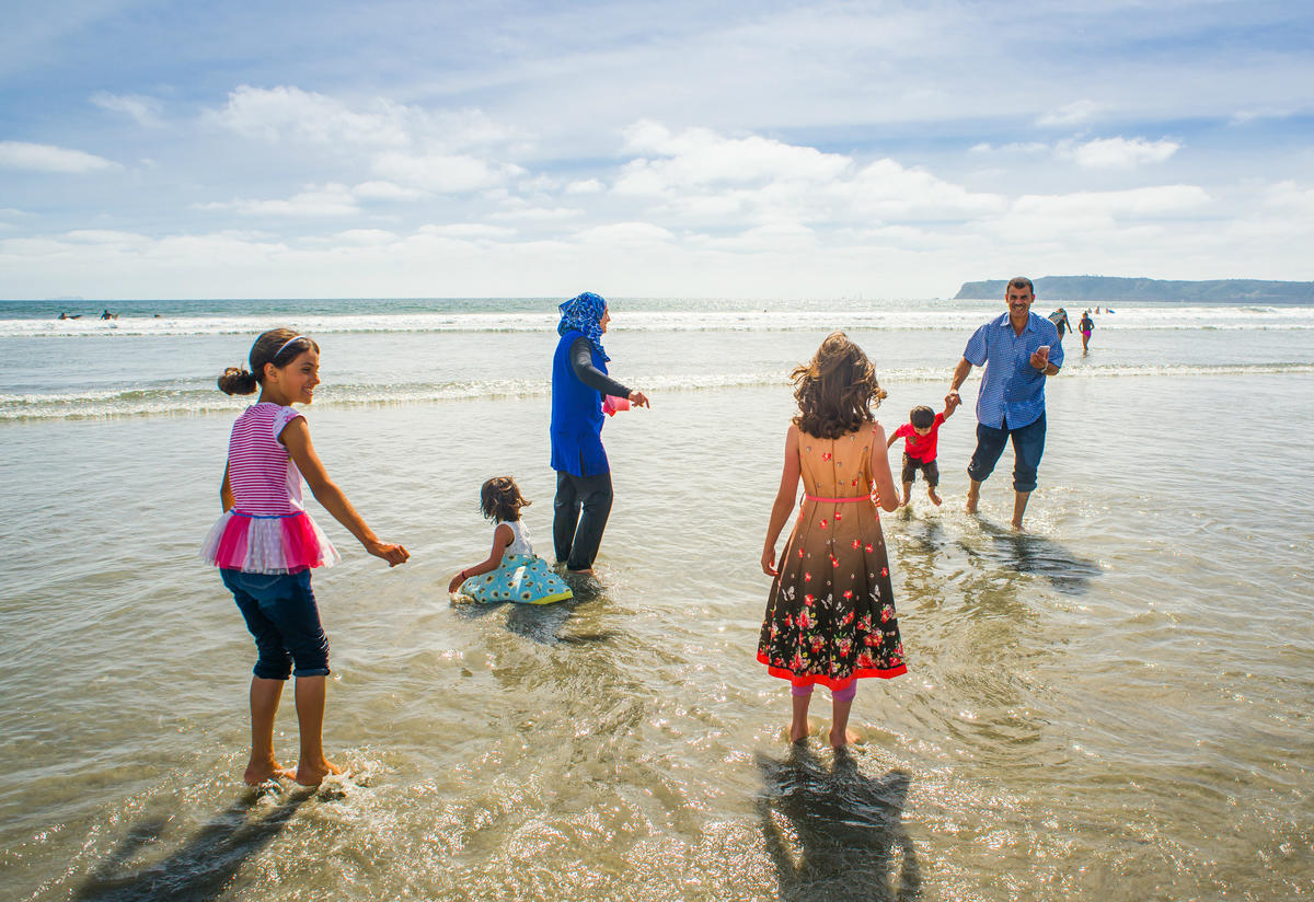 Azzam and Nisreen Tlas and their children play in the surf on a California beach