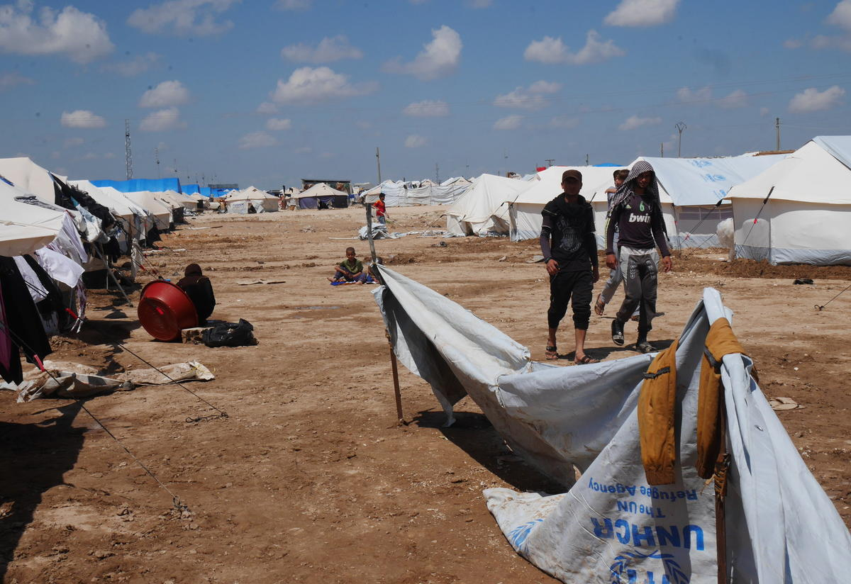 Iraqi refugees walk along a row of tents in Al Hol camp in northeast Syria.