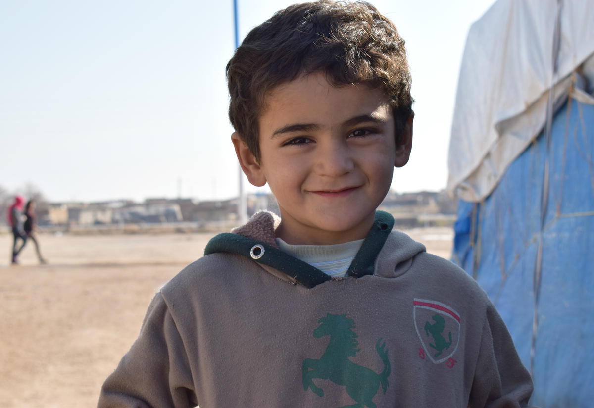 The three-year-old grandson of Yazidi couple Suleiman and Khabshe, outside a tent at Newroz refugee camp