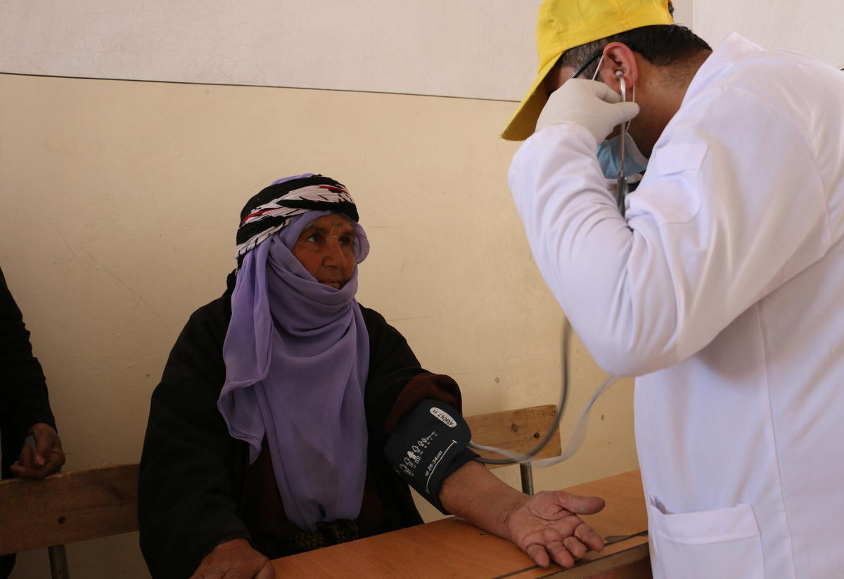 An IRC nurse checks a patient's blood pressure during a mobile clinic day in northeast Syria.